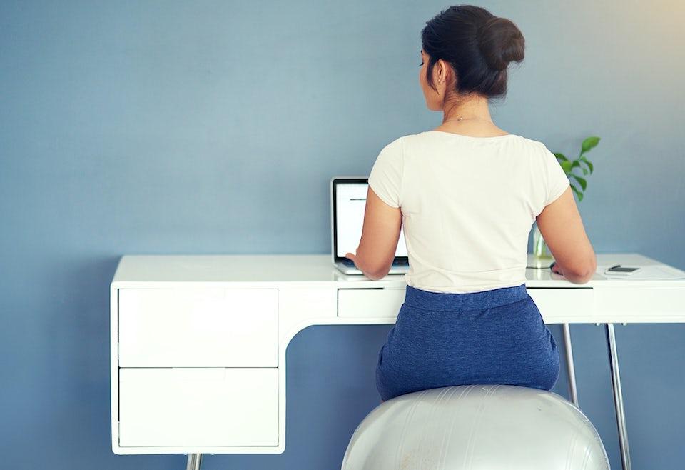Nainen tekee kotitoimistossa läppärillä töitä jumppapallolla istuen