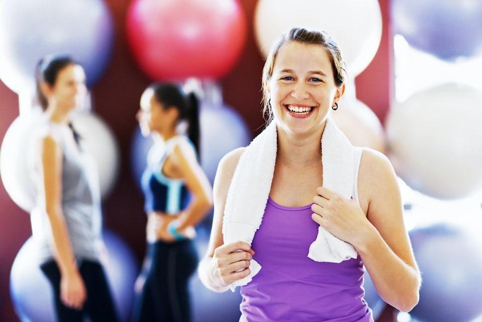 Kvinne står med håndkle og smiler