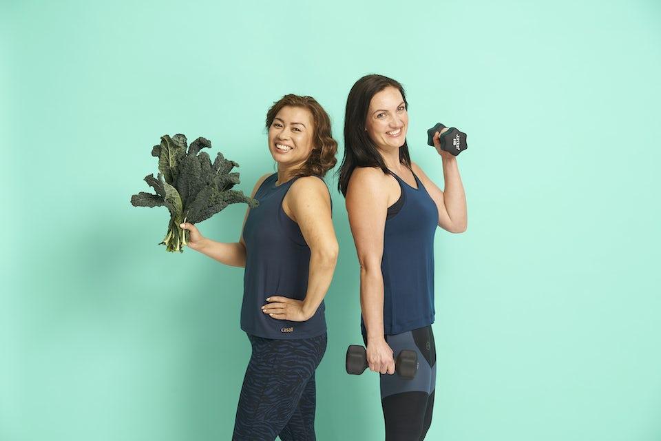 Kvinnor står med grönsaker och hantlar