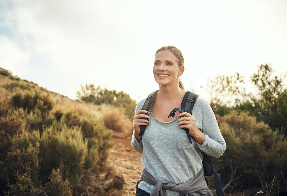 Nainen reippailee luonnon helmassa reppu selässä