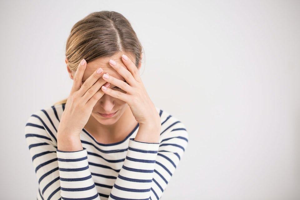 Kvinna med OCD håller sig för pannan