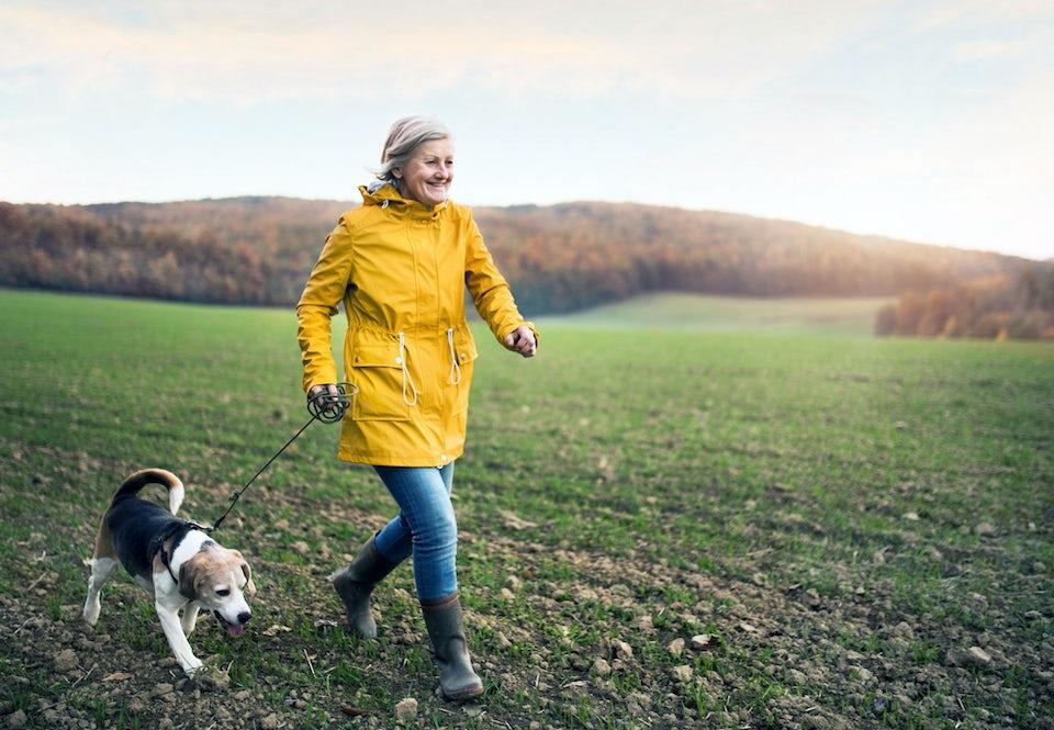 Nainen reippaalla kävelylenkillä koiran kanssa.