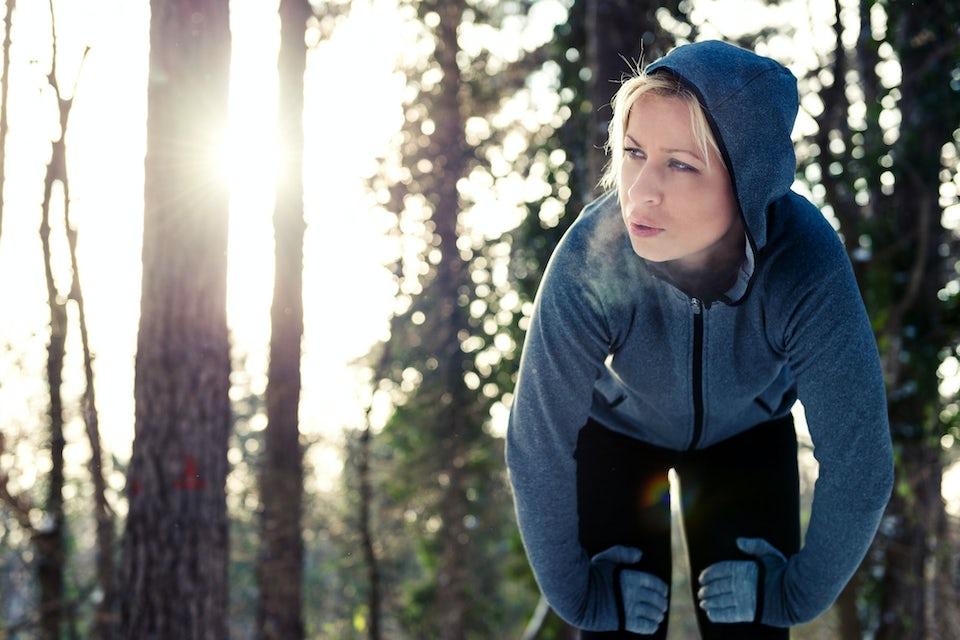 Nainen nojaa jalkoihinsa kovavauhtisen juoksun jälkeen - suuri energiankulutus