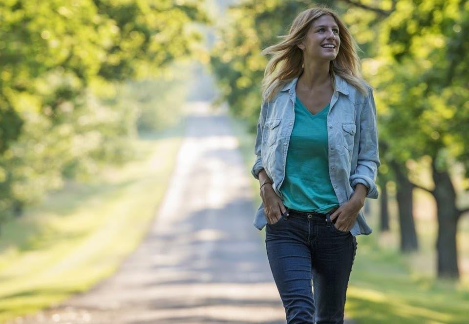 Nainen kävelee kesällä auringossa