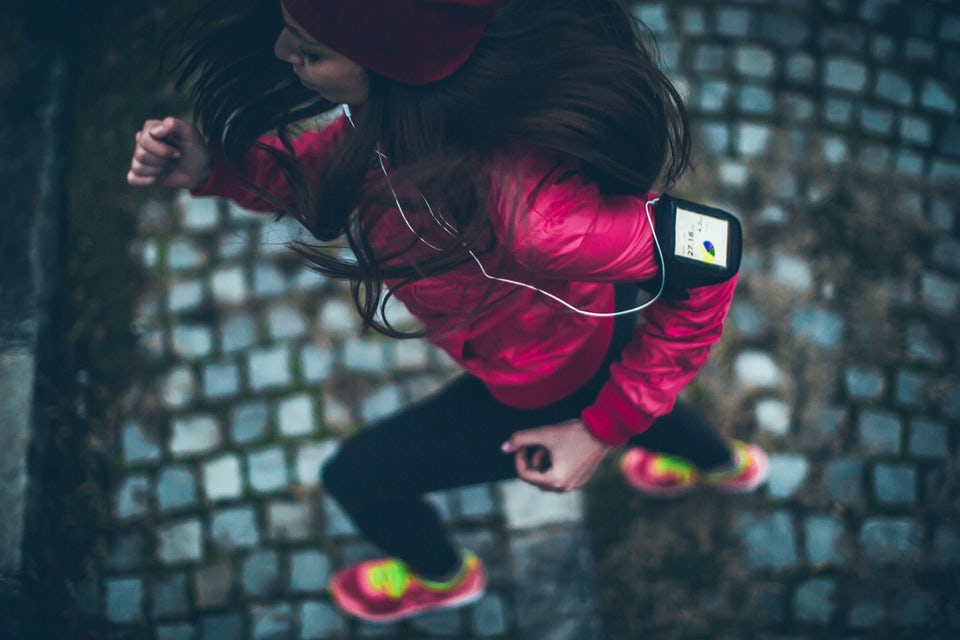 Kvinna springer med telefon på armen