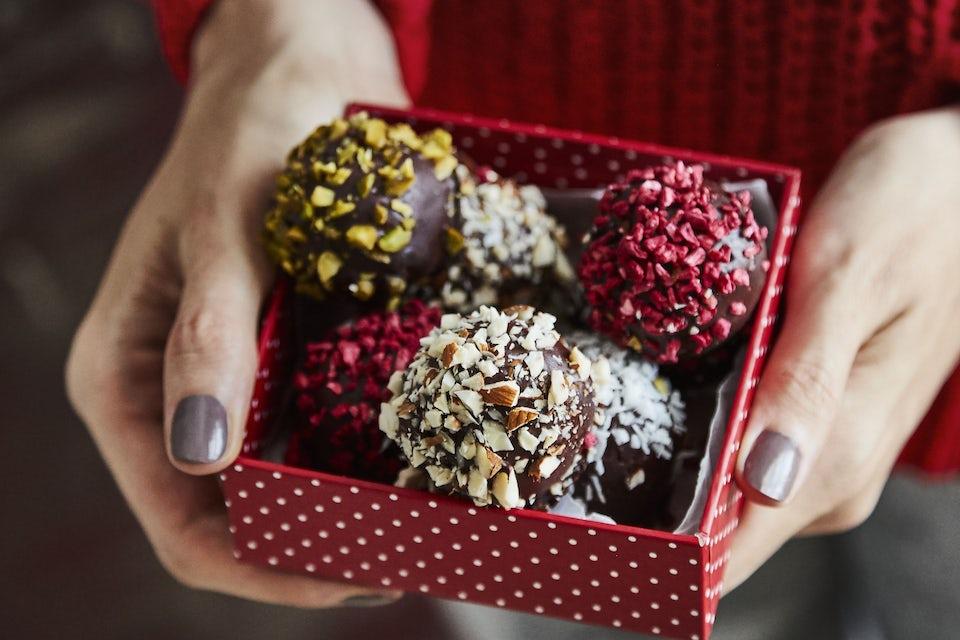 Värikkäästi koristeltuja suklaa-taatelikuulia punaisessa rasiassa