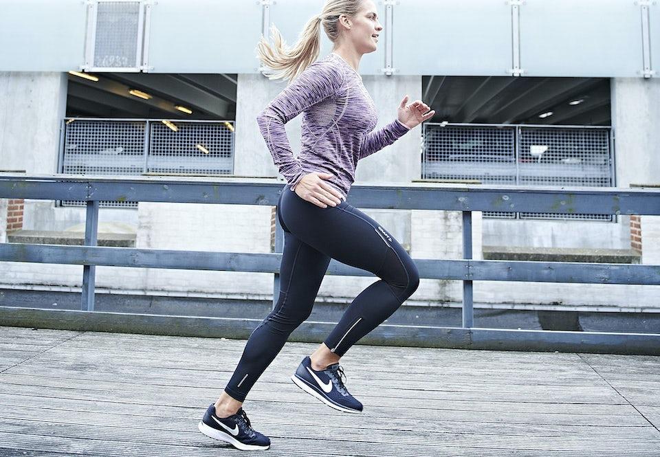Nainen juoksee juoksutrikoot yllään