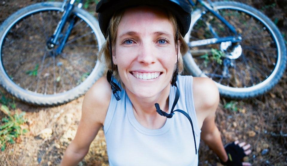 Nainen istuu maastopyörän edessä metsässä