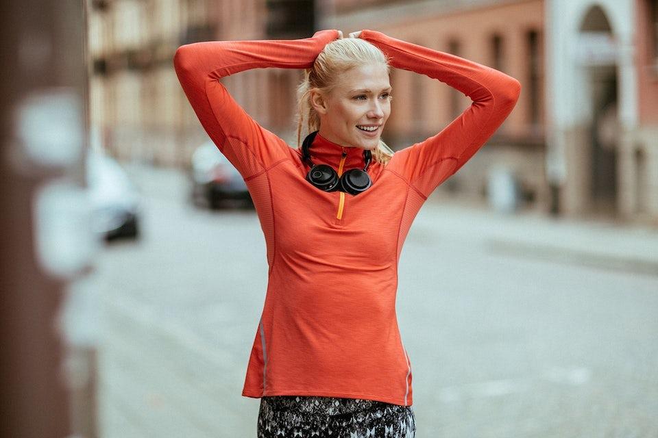 Nainen juoksuvaatteissa, kuulokkeet kaulalla