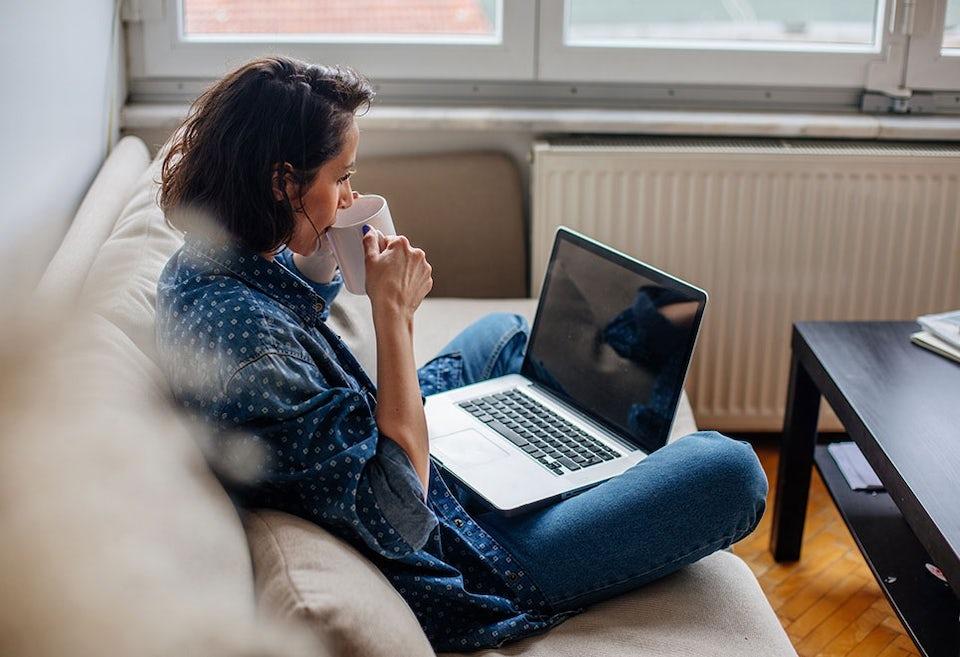 Kvinne sitter i en sofa, ser tankefullt ut i lufta
