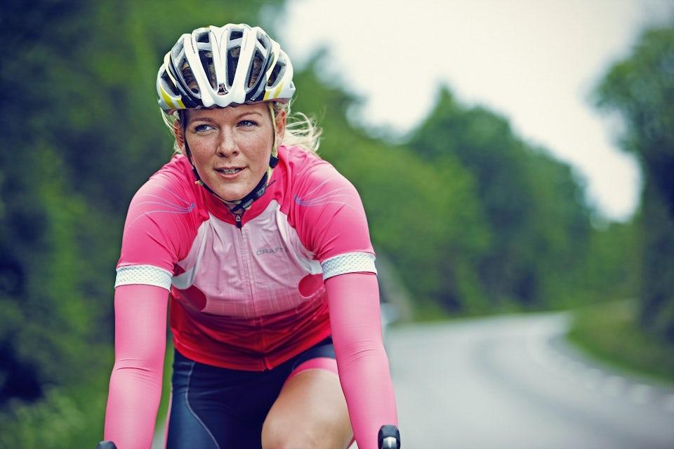 Nainen pyöräilee maantiellä