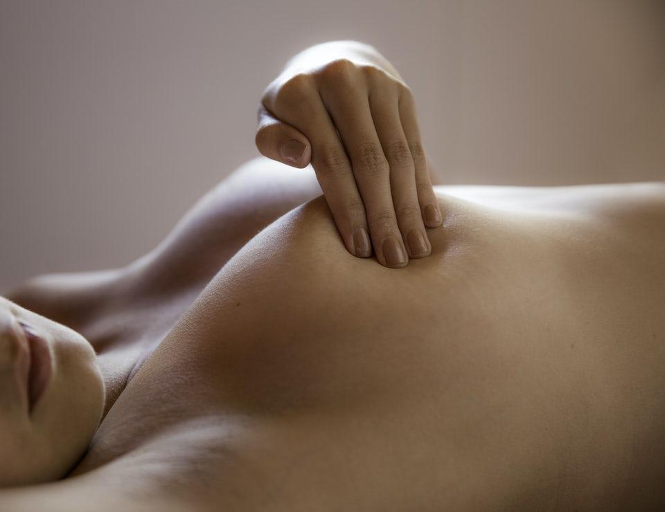 Nainen tunnustelee rintaansa selinmakuulla.