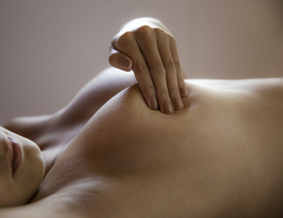 Kvinde masserer brystet sitt mens hun ligger på ryggen.