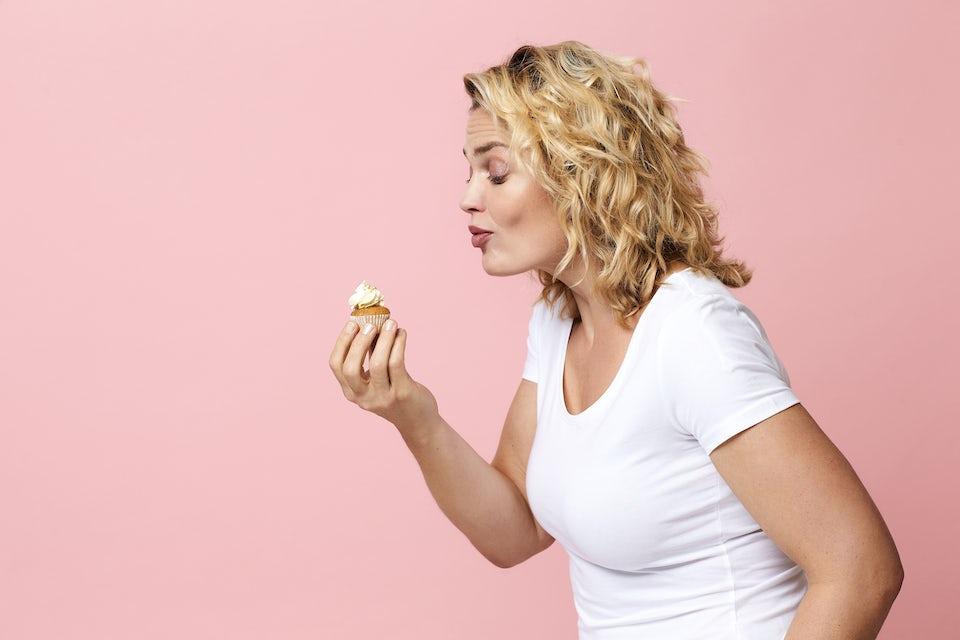 Kvinne ser forelsket på en cupcake