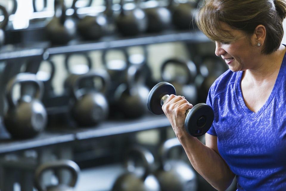 Kvinde i overgangsalder styrketræner med håndvægt.
