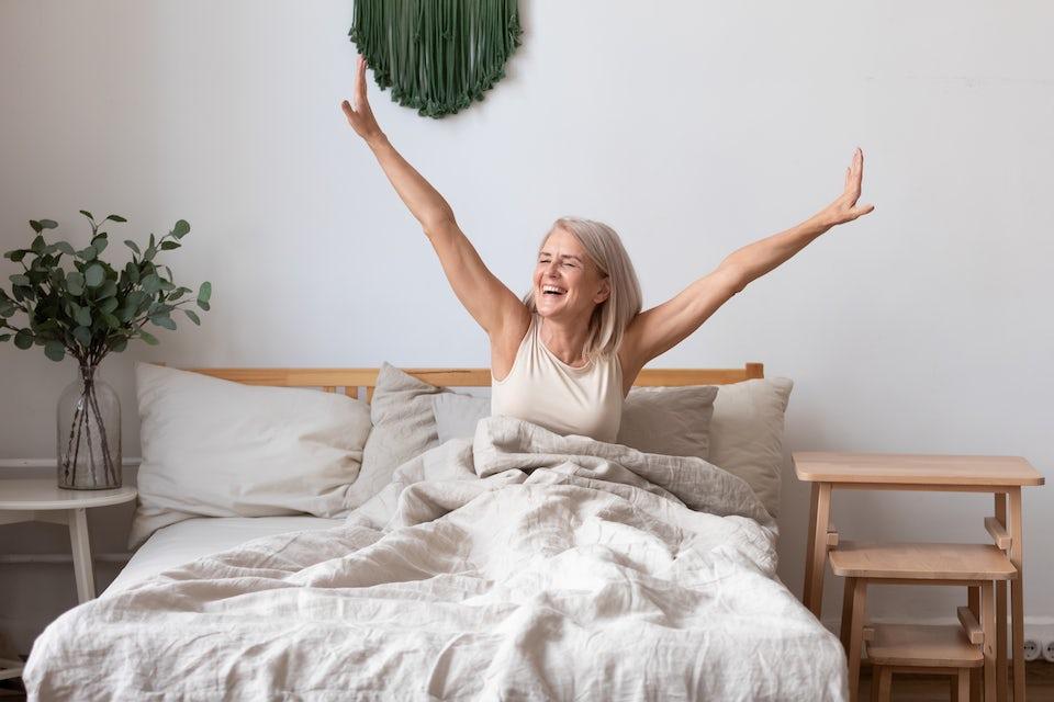 Udhvilet kvinde sidder i sengen