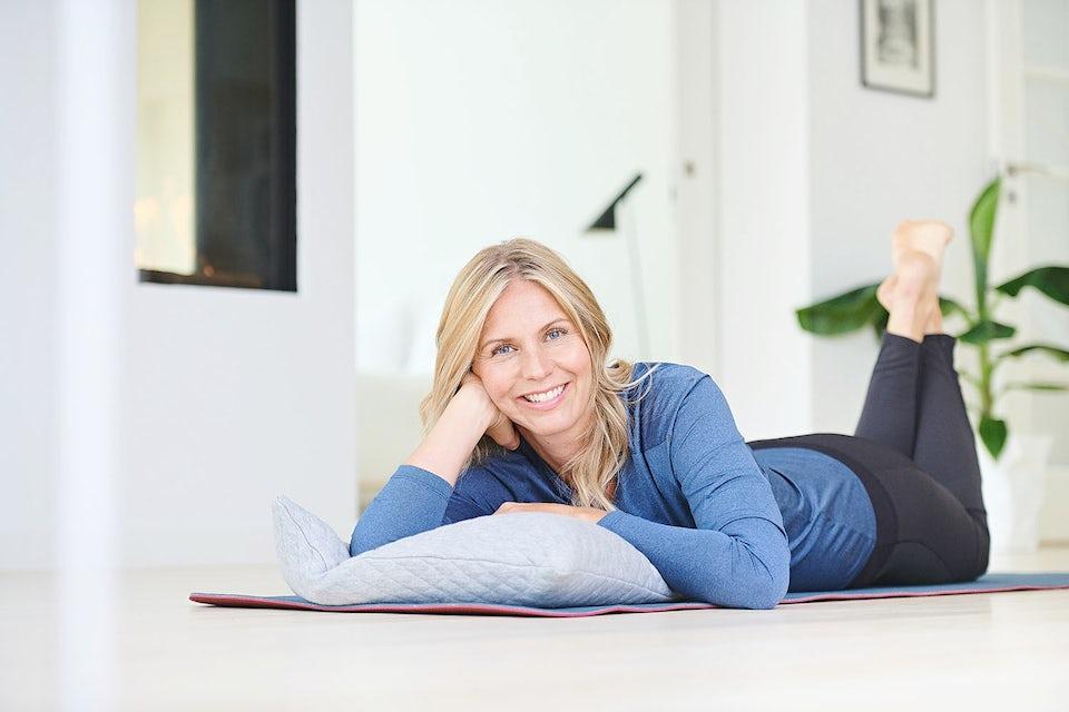 Smilende kvinne i overgangsalderen ligger på gulvet og slapper av.