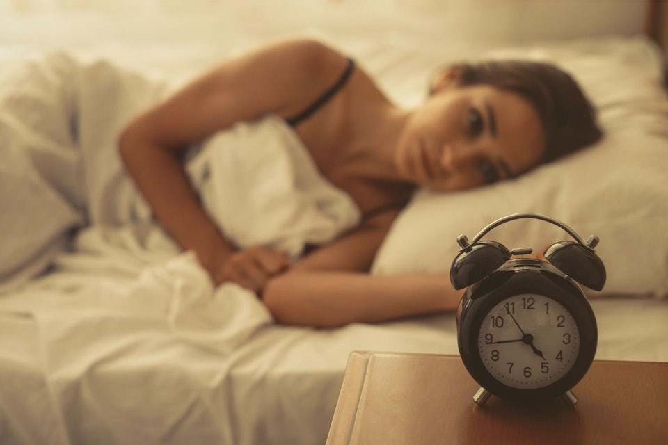 Uni - nainen makaa unettomana sängyssä