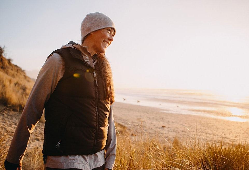 Nainen seisoo rannalla kävelylenkillä
