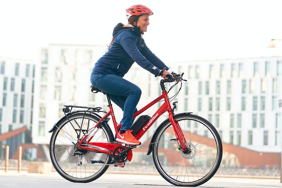 Nainen pyöräilee punaisella sähköpyörällä