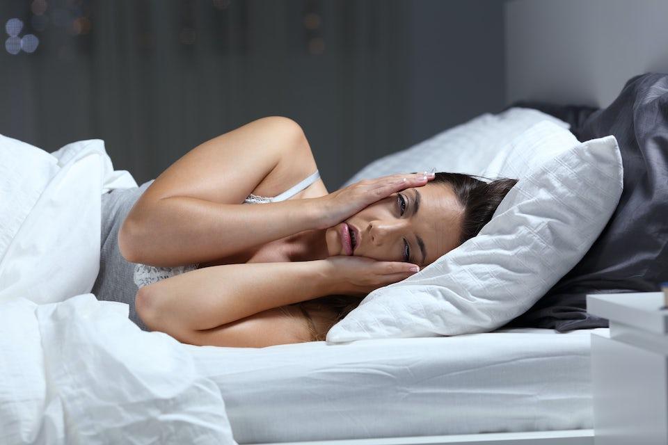 Kvinna ligger i sängen och har ont – smärtstillande medicin