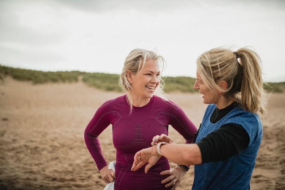 To smilende kvinner på stranda, begge har aktivitetsklokker