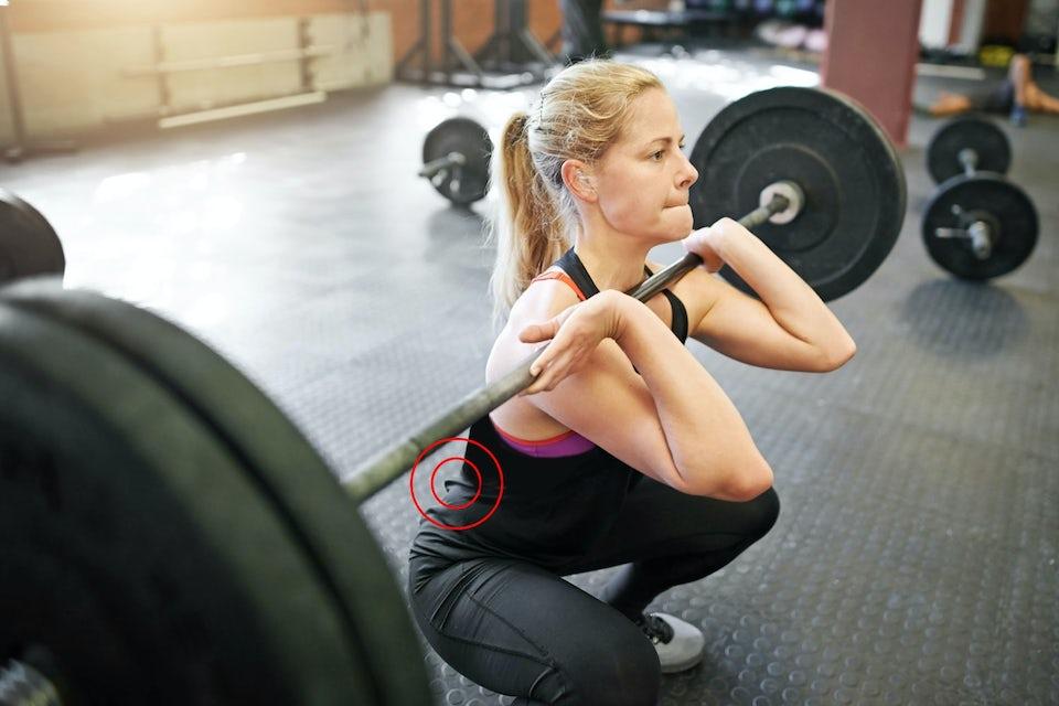 Kvinna lyfter vikter, fokus på rygg, diskbråck.