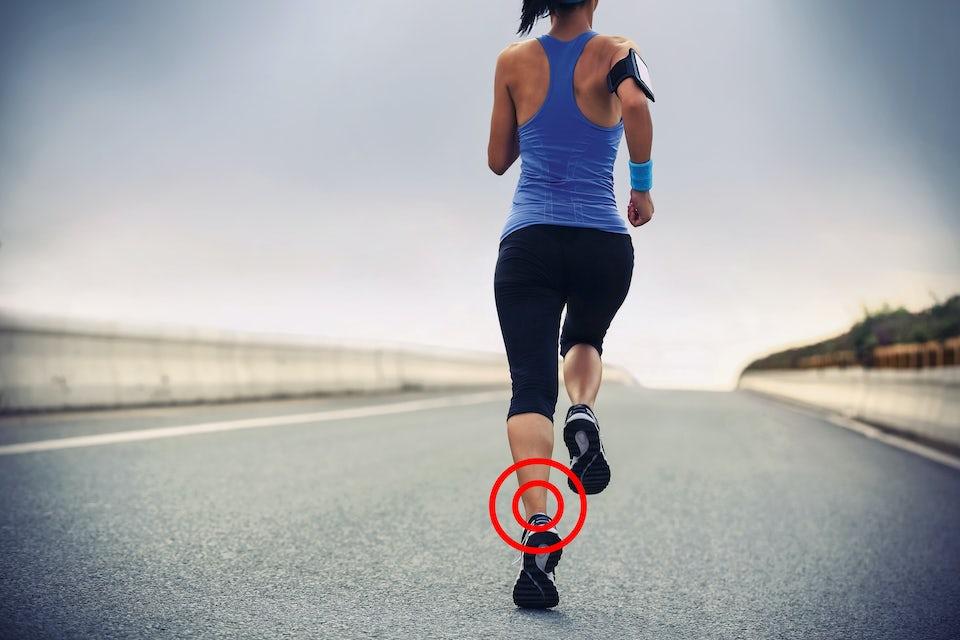 Nainen juoksee maantiellä, akillesjänne ympyröity