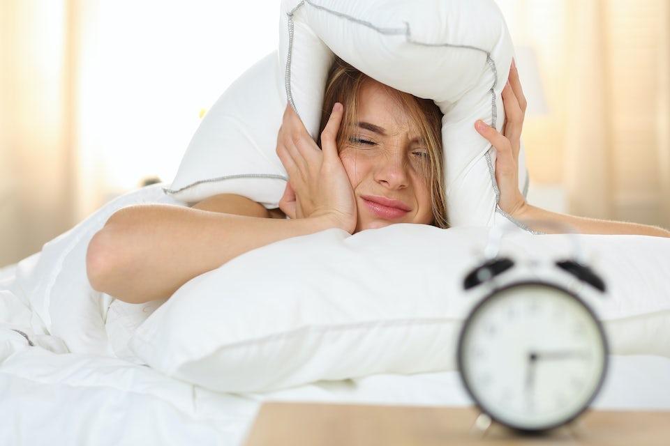 Trött kvinna tittar på väckarklockan efter byte till sommartid