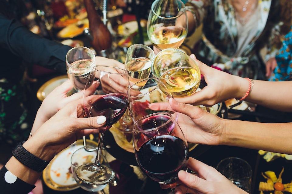 Människor skålar med rödvin och champagne