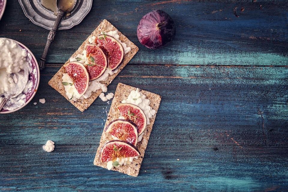 Et sundt mellemmåltid af knækbrød med hytteost og figen