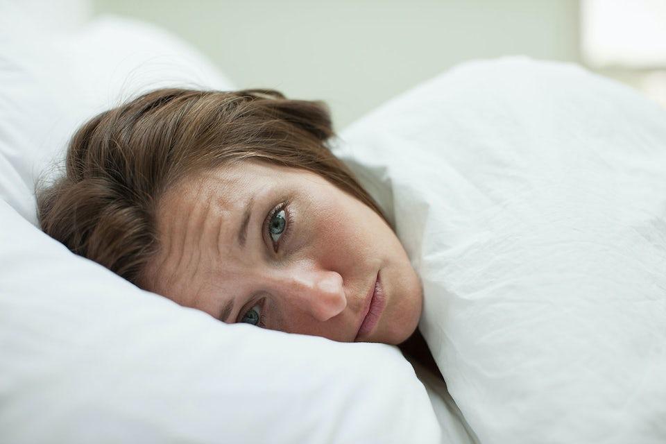 Stresset kvinne ligger søvnløs isenga.