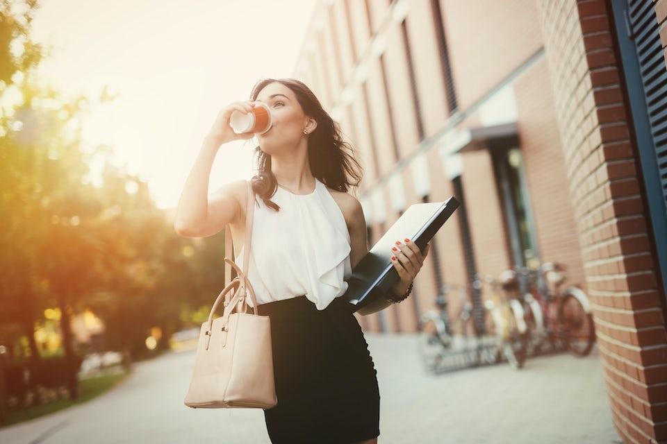 Nainen laukku olkapäällä ja tietokone kädessä juo kahvia kävellessään - kortisoli, stressi