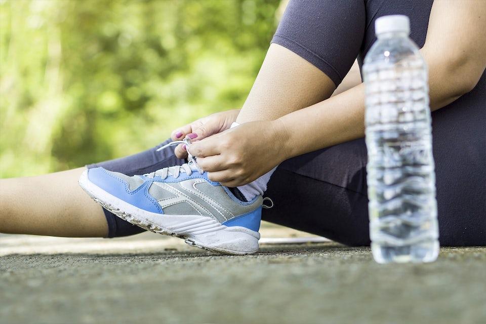 Nainen solmii lenkkareita, vesipullo mukana