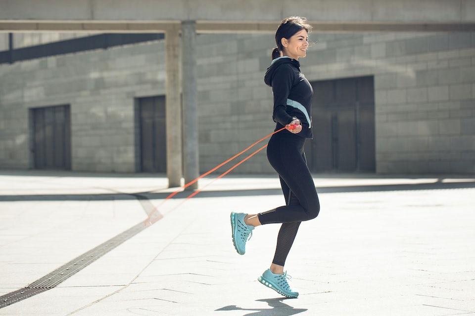 Kvinna tränar med hopprep utomhus.