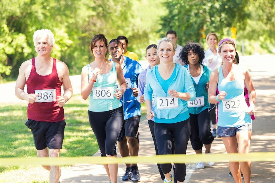 Naiset ja miehet juoksevat numerolaput paidoissa
