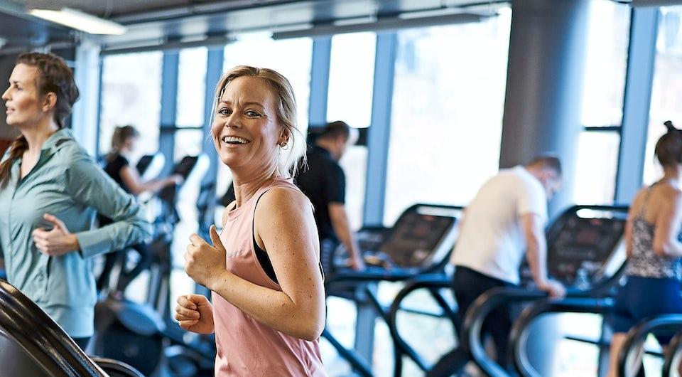 Smilende kvinder på løbebånd - forebygger slagtilfælde med motion