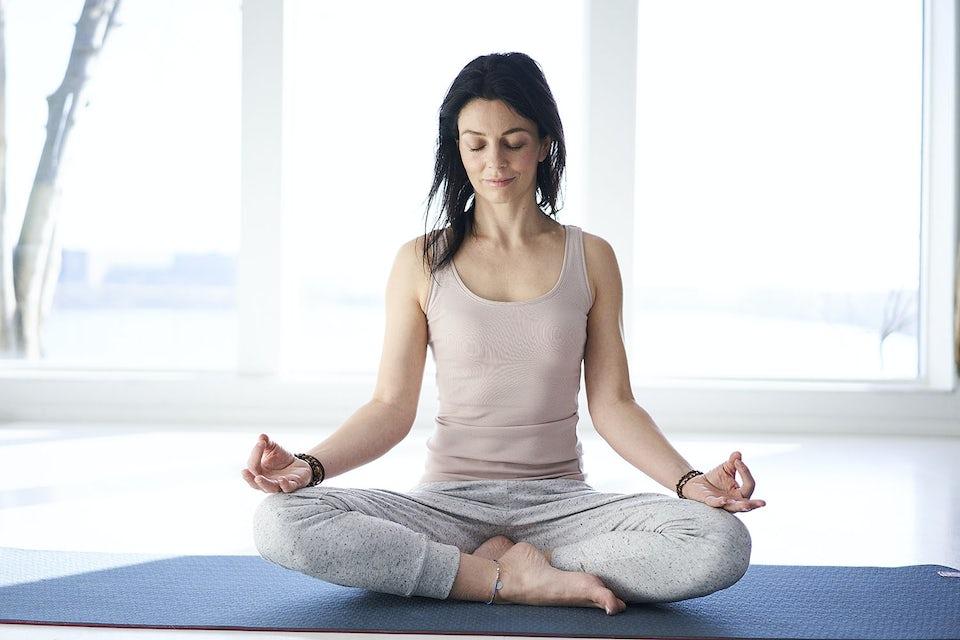 Kvinne mediterer på en yogamatte