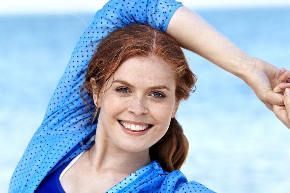 Rödhårig kvinna ler, malignt melanom