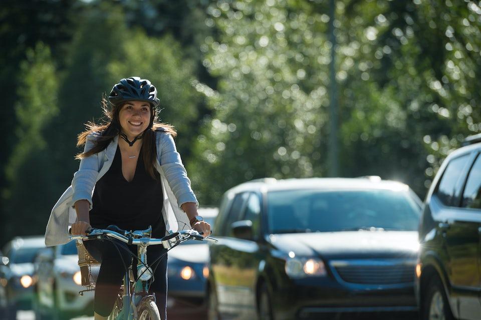Kvinde på cykel i hverdagstøj.