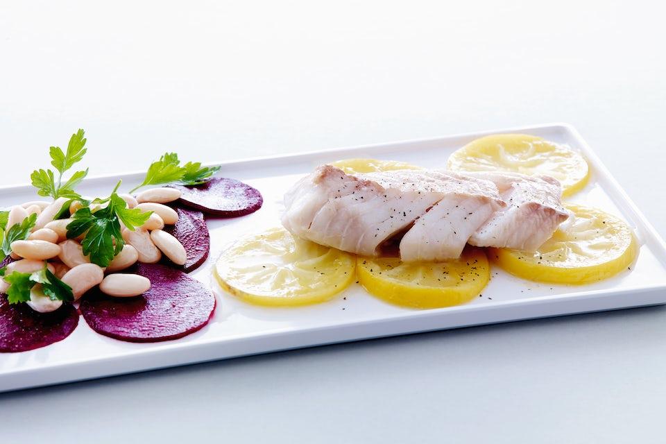 Kalaa, punajuurta ja valkoisia papuja lautasella.