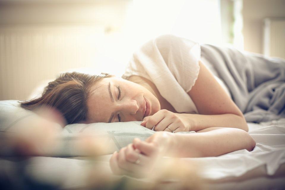 Kvinde, der ligger i sin seng og sover dyb søvn