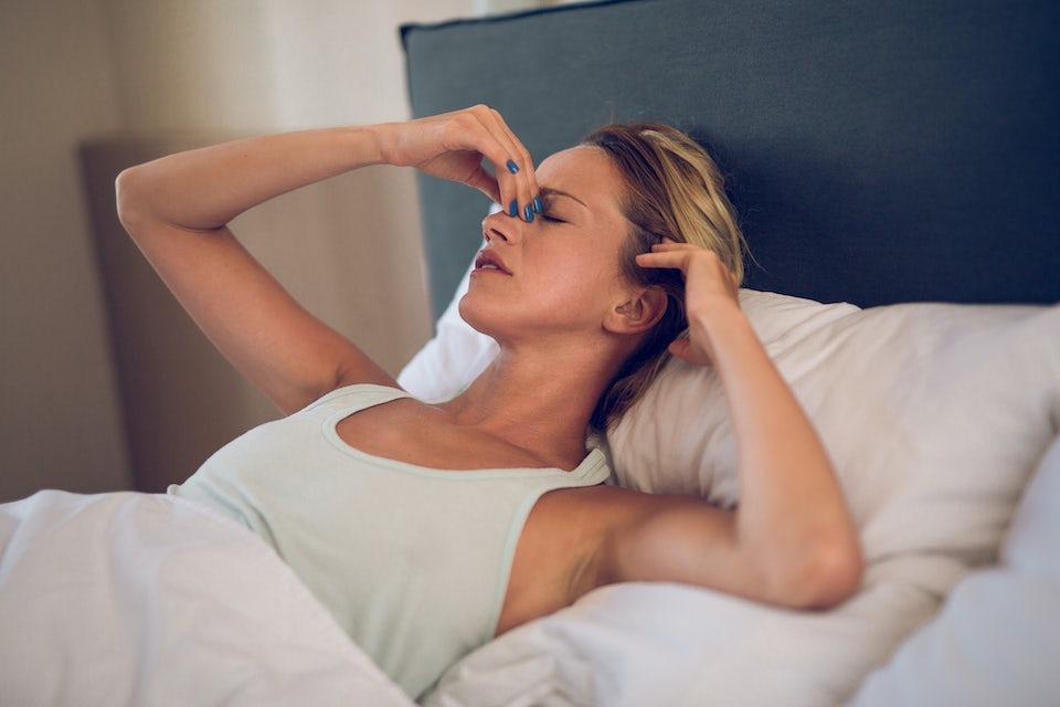 Kvinne med bihulebetennelse tar seg til nesa på grunn av smerter