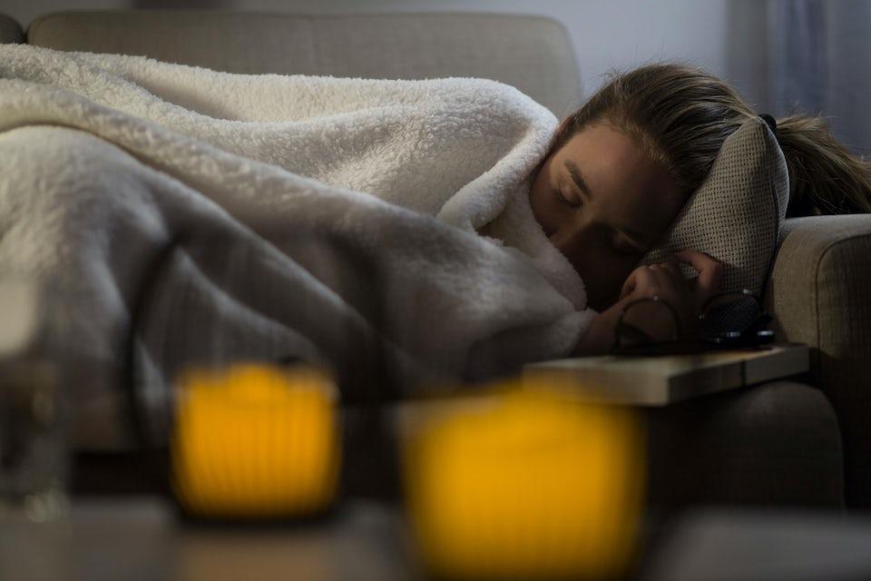Kvinna med lunginflammation ligger på soffan och sover
