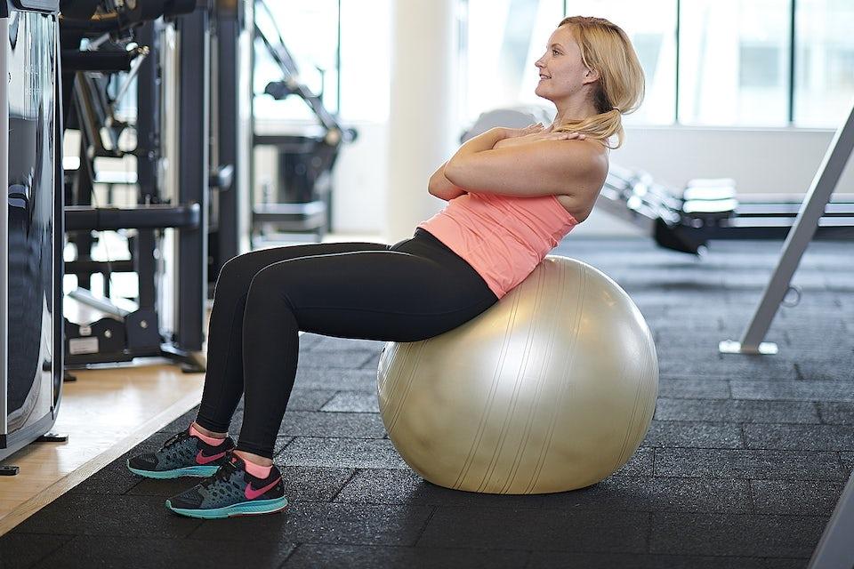 Nainen treenaa jumppapallolla, hoikistu kuntosalitreenillä