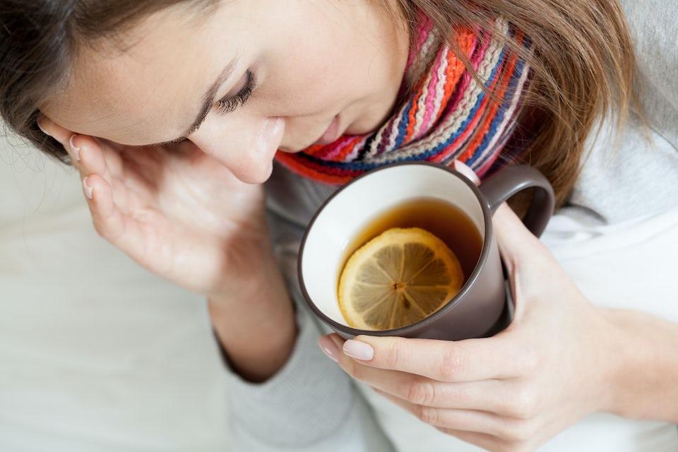 Kvinne med halsbetennelse tar seg til hodet, drikker te.