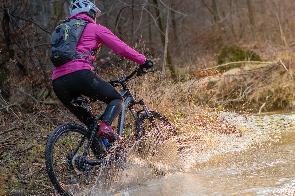 Kvinna kör mountainbike i skogen
