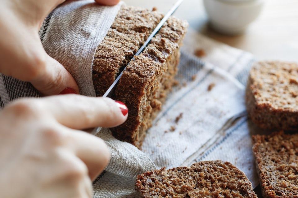 Kvinne skjærer rugbrød