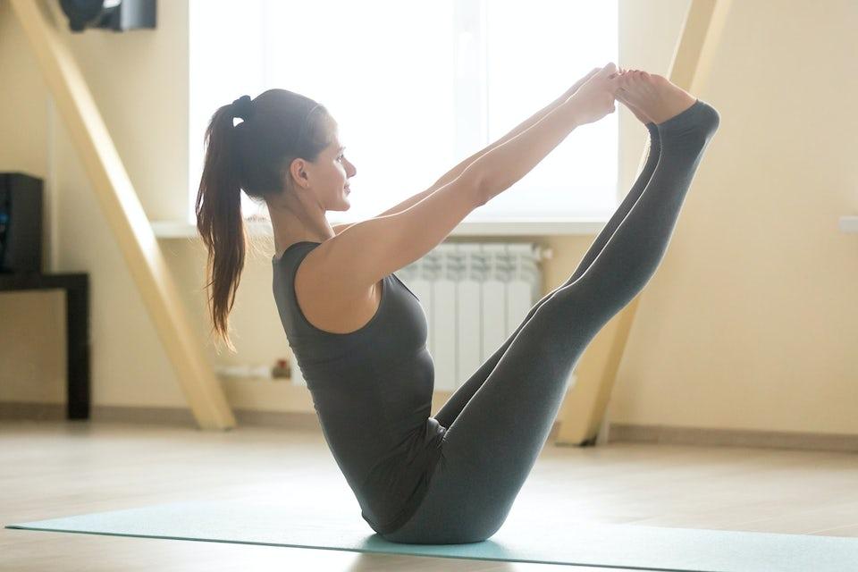 Kvinna sitter i balansövning på golvet