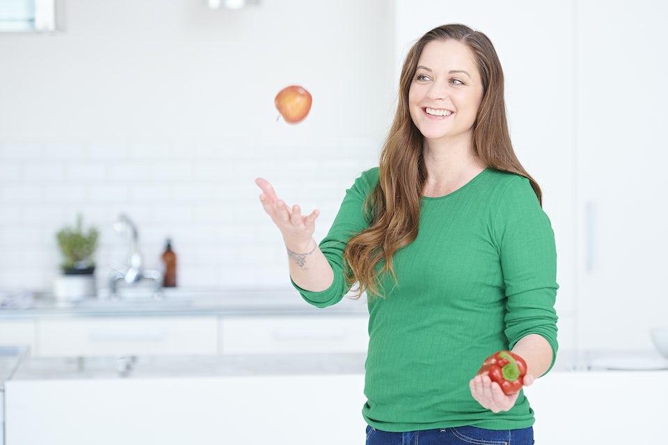 Kvinne kaster frukt og grønt i været